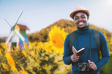 Smiling African Traveler Holding Passport With Sunflowers Field In Background