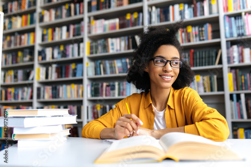Photo Teenage african american female pretty student with glasses, studying while sits