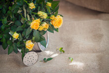 Bouquet Of Yelloow Roses In Watering Can On Background Of Old Burlap