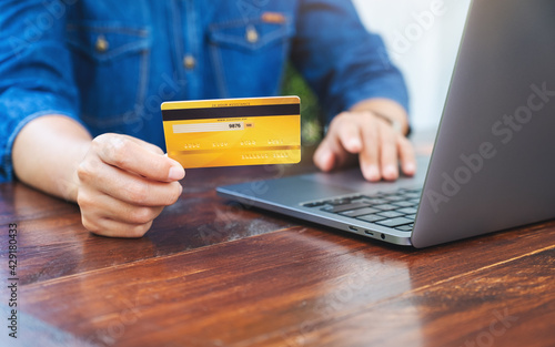 Closeup image of a woman holding credit cards while using laptop computer for online shopping