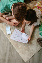 Top View Of Unrecognizable Kids Playing Treasure Hunt At Home On The Carpet