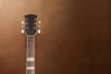 Fragment Of A Neck With The Headstock Of An Acoustic Guitar On A Blurred Background.
