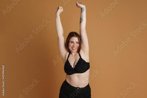Smiling young plus size woman wearing bra posing
