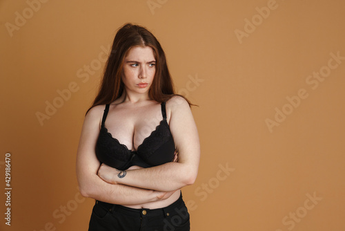 Young displeased woman wearing brassiere posing with arms crossed