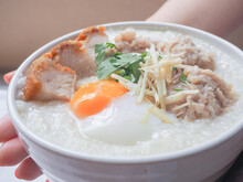 Holding Bowl Of Rice Porridge With Minced Pork, Soft-boiled Egg, Sliced Ginger And Deep-fired Pork