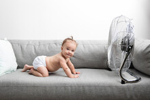 Funny Baby In Diaper Facing Electric Fan On Sofa