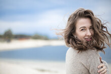Portrait Of A Beautiful Sensual Young Woman, Hair Develops The Wind, Brunette With Emotions, Hands Hair And Face, Seaside Wind Outside