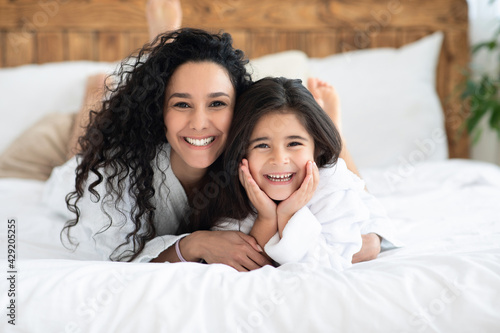 Cheerful caucasian mother and daughter bonding on bed
