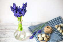 Spring Decorative Composition. Miniature Grape Hyacinth Flowers In A Glass Vase. Easter Decoration.