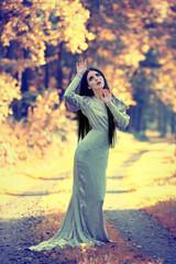Kobieta w długiej sukni na leśnej ścieżce