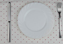 White Empty Plates And Cutlery On Polka Dot Napkin On White Wooden Table. Setting Table Top View.