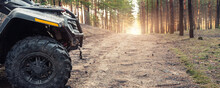Clode-up Side Of ATV Awd Quadbike Motorcycle Profile View Dirt Country Forest Road Beautiful Nature Morning Sunrise Landscape. Offroad Travel Adventure Trip Expedition. Extreme Recreation Activity