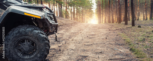 Canvas Print Clode-up side of ATV awd quadbike motorcycle profile view dirt country forest road beautiful nature morning sunrise landscape