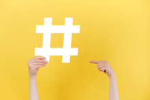 Horizontal Images Of Female Hands Holding And Pointing On Large Big Hashtag Sign, Viral Web Content, Internet Promotion, Isolated Over Yellow Studio Wall. Blogging Blog Website Strategy Concept