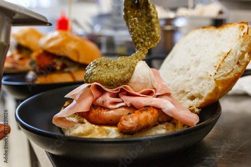 Fotografie, Obraz Panino da pub con salsiccia, mortadella e mozzarella mentre viene guarnito con p