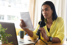 Mixed Race Transgender Woman Making Podcast Using Microphone And Laptop, Reading Notes