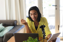 Mixed Race Transgender Woman Making Podcast Using Microphone And Laptop, Talking, Holding Notes