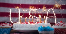 Composition Of Sparkling Usa Text Over Birthday Cake And Cupcakes Over American Flag