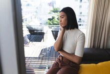 Mixed Race Transgender Woman Sitting In Thought In Living Room On Sunny Day