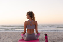 Rear View Of Of Caucasian Woman Meditating And Practicing Yoga While Sitting On Yoga Mat At The Beac