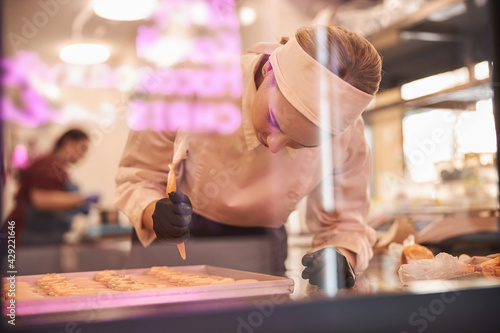 Fototapeta Inspired pastry chef making macarons in stylish modern kitchen space