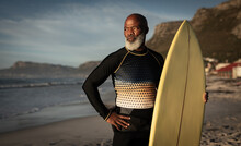 Portrait Of African American Senior Man On Beach Holding Surfboard Looking Out To Sea