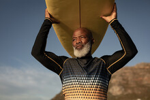 Senior African American Man Carrying Surf Board On His Head On The Beach