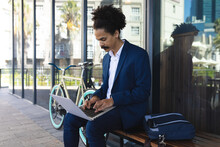 Mixed Race Male With Moustache Sitting On Bench In Street Using Laptop