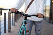 Mid Section Of Mixed Race Male Wheeling Bicycle In The Street