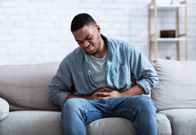 Black Guy Having Painful Stomachache Touching Aching Stomach Sitting Indoors