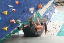 Caucasian Woman Wearing Mask Climbing Up A Wall At Indoor Climbing Gym