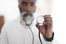 African American Senior Male Doctor Wearing White Coat Looking At Camera Holding Stethoscope
