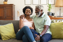 Smiling African American Senior Couple Sitting On Sofa And Embracing In Living Room