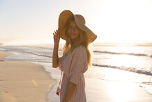 Caucasian Woman Wearing Beach Cover Up And Hat Having Fun At The Beach