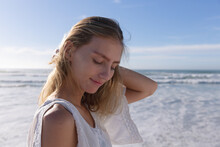 Smiling Caucasian Woman Standing With Eyes Closed At The Beach