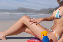 Caucasian Woman Wearing Bikini Sitting On Towel Putting Sunscreen On At The Beach
