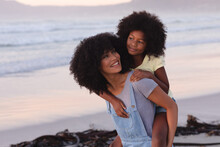 Smiling African American Mother Carrying Her Daughter Piggyback At The Beach