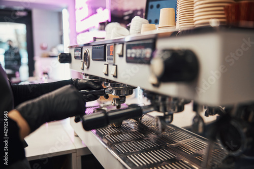 Busy barista operating a modern coffee machine at cafe Fototapet