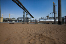 Kzylorda Region/Kazakhstan - May 01 2012: Modern Gas Power Plant In  Desert. Heat Exchanger, Pipelines And Chimneys. Yellow Sand On Foreground.