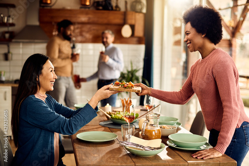 Canvastavla Happy African American woman serving appetizer while setting table for lunch with her friends at home