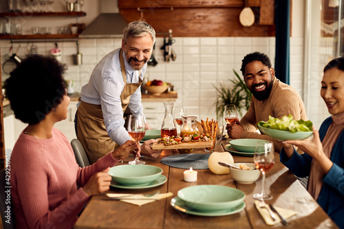 Fotografiet Happy man serving appetizer while having lunch with his friends at home