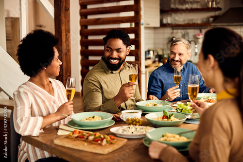 Fotografie, Obraz Happy black man drinking wine and enjoying in lunch with his friends at dining table