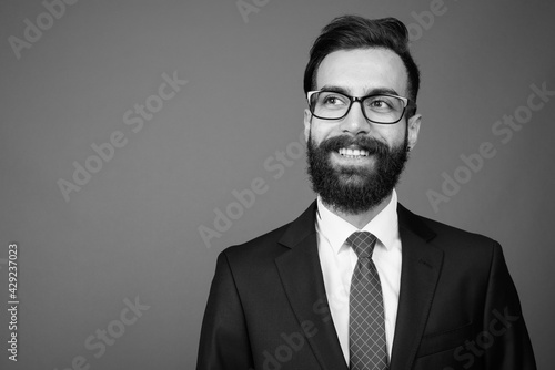 Young handsome bearded Persian businessman against gray background - fototapety na wymiar