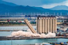 Demolition Of A Large Agricultural Consortium Building In Cagliari, Sardinia. 45 Degrees Shot During The First Explosion And Fall Of The Silos. Tearing Down Of A Structure Near The Sea.