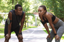 Tired African Couple Taking Breath After Hard Workout Outdoors, Resting Together