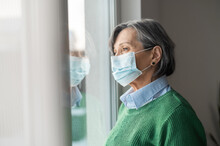 A Senior Middle-aged Gray-haired Woman Wearing Green Sweater And Protective Face Mask Looking At The Window And Feeling Sad Depressed And Lonely During Coronavirus Pandemic, Lockdown Struggles Concept