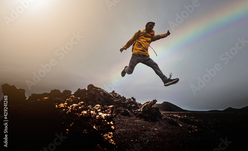 Foto Man jump through the gap over the mountain rocks at sunset