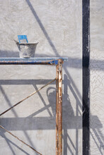 Cement Bucket With Plastering Tools On Scaffolding With Sunlight And Shadow On Concrete Wall Surface Inside Of House Construction Site In Vertical Frame