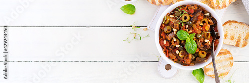 Traditional Italian Caponata and toast on a wooden white table Fototapet