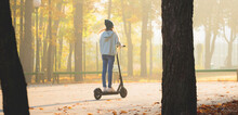 Girl On Scooter In Autumn Park